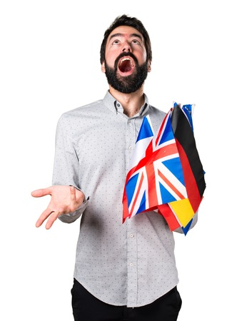 bilingual: Handsome man with beard holding many flags and making surprise gesture Stock Photo