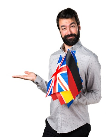 bilingual: Handsome man with beard holding many flags and holding something