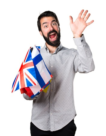 bilingual: Handsome man with beard holding many flags and saluting Stock Photo