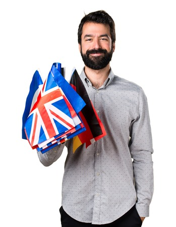 bilingual: Handsome man with beard holding many flags Stock Photo