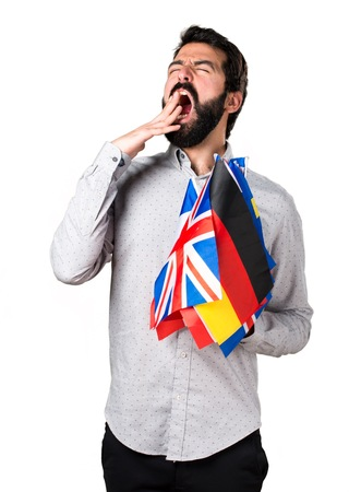 bilingual: Handsome man with beard holding many flags and yawning Stock Photo