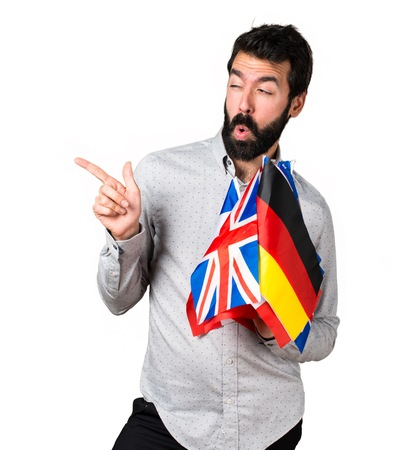 bilingual: Handsome man with beard holding many flags and pointing to the lateral