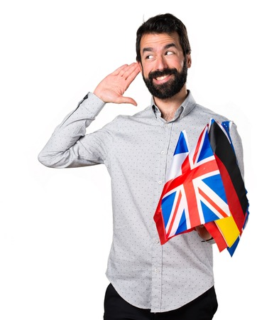 Handsome man with beard holding many flags and listening something Stock Photo
