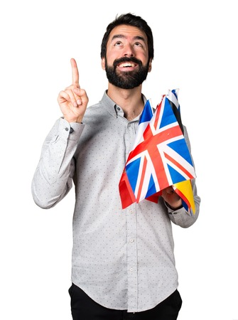 bilingual: Handsome man with beard holding many flags and pointing up