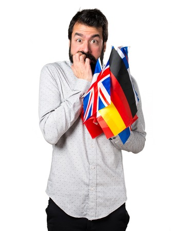 bilingual: Frightened handsome man with beard holding many flags