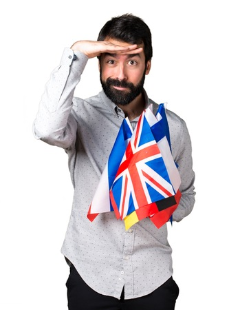 bilingual: Handsome man with beard holding many flags and showing something