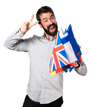 bilingual: Handsome man with beard holding many flags and making victory gesture