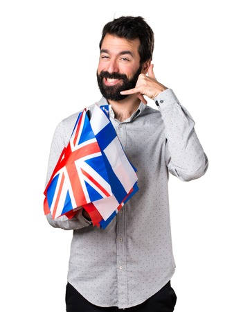 bilingual: Handsome man with beard holding many flags and making phone gesture Stock Photo