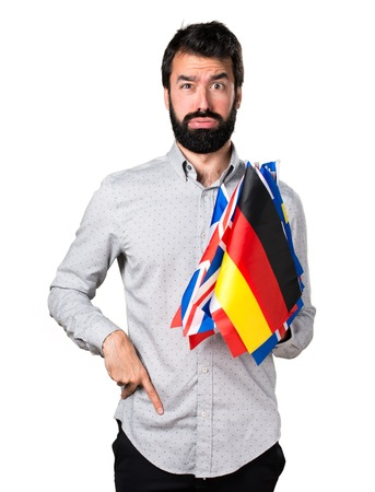 bilingual: Tired handsome man with beard holding many flags