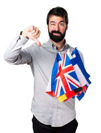 bilingual: Handsome man with beard holding many flags and making bad signal