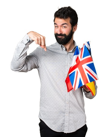 bilingual: Handsome man with beard holding many flags and pointing down