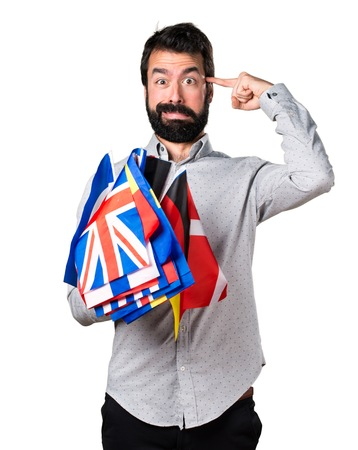bilingual: Handsome man with beard holding many flags and making crazy gesture Stock Photo