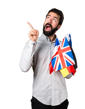 bilingual: Handsome man with beard holding many flags and thinking