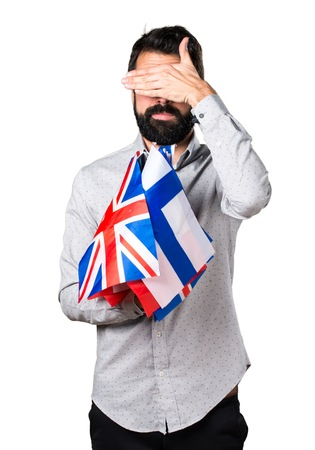 bilingual: Handsome man with beard holding many flags and covering his eyes Stock Photo