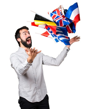 bilingual: Happy handsome man with beard holding many flags Stock Photo