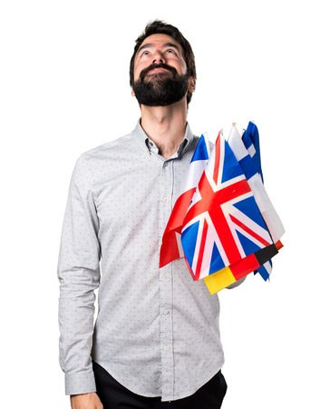 bilingual: Handsome man with beard holding many flags and looking up Stock Photo