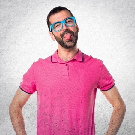 mockery: Man with colorful clothes making a joke on grey textured background Stock Photo
