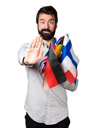 bilingual: Handsome man with beard holding many flags and making stop sign