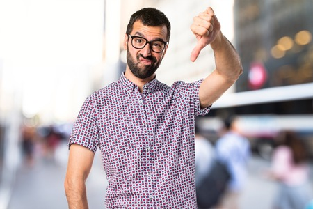 Man with glasses doing bad signal