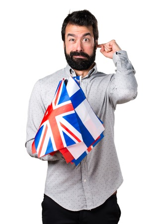 bilingual: Handsome man with beard holding many flags and covering his ears