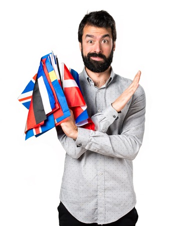 bilingual: Handsome man with beard holding many flags and making NO gesture Stock Photo