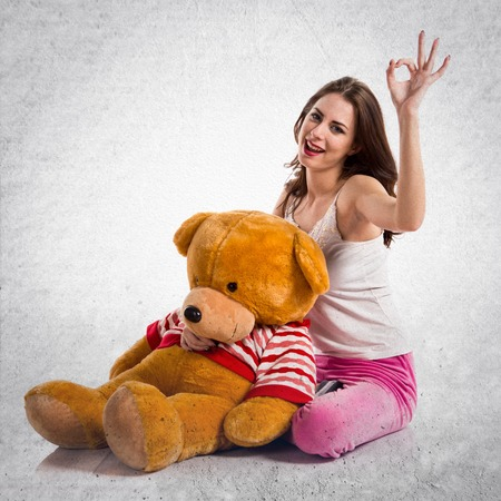 Girl with pajamas making OK sign and playing with stuffed animal on textured grey background