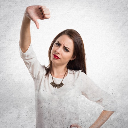 disapprove: Pretty young girl making bad signal on textured grey background