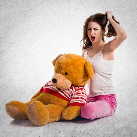 angry teddy: Frustrated pretty brunette girl with pajamas on textured grey background