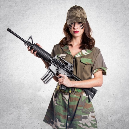 Military woman holding a rifle on textured grey background