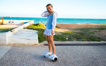 Beautiful blonde girl playing with a hoverboard
