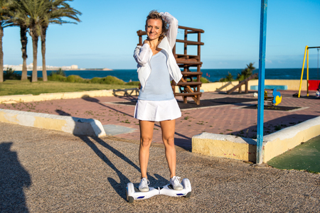 motorizado: Beautiful blonde girl playing with a hoverboard