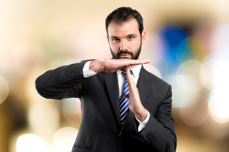 Young man doing the timeout sign over white background