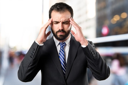 Young businessman with headache over white background Stock Photo