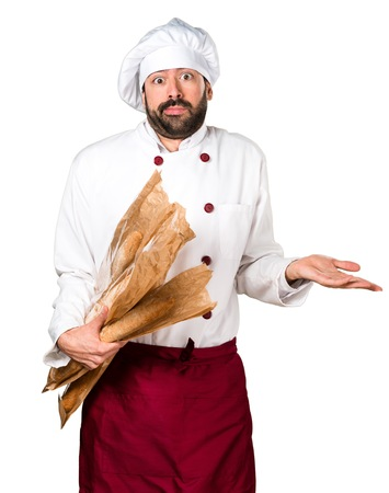 Young baker holding some bread and making unimportant gesture Stock Photo