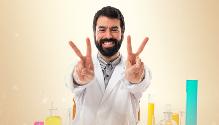 Scientist man doing victory gesture on ocher background