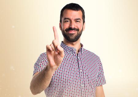 Hombre guapo contando uno sobre fondo ocre