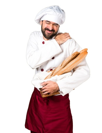 Young baker holding some bread with shoulder pain Stock Photo