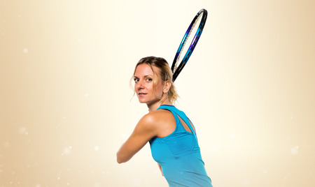 Blonde woman playing tennis on ocher background