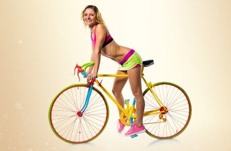 Beautiful blonde woman with colorful bike on ocher background