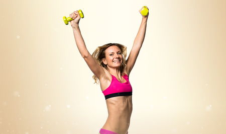 Sport woman making weightlifting on ocher background