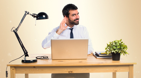 Businessman in his office listening something on ocher background