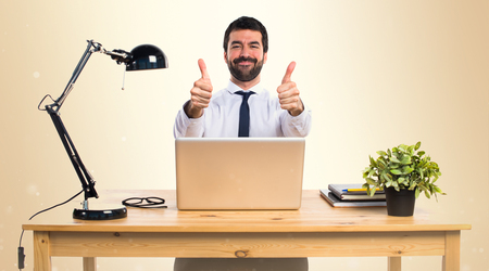 Businessman in his office with thumb up on ocher background Stock Photo