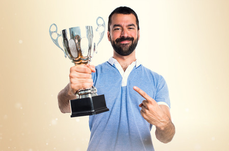 Man with blue shirt holding a trophy on ocher background