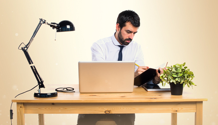 Businessman in his office writting notes on ocher background Stock Photo