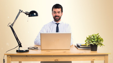 Businessman working with laptot in his office on ocher background Stock Photo