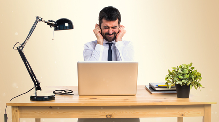 Businessman in his office covering his ears on ocher background