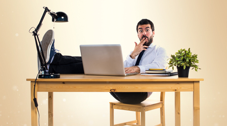 Handsome businessman in his office on ocher background