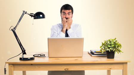 Frightened businessman in his office on ocher background Stock Photo