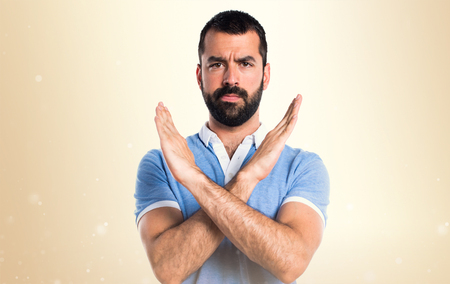 Man with blue shirt doing NO gesture on ocher background