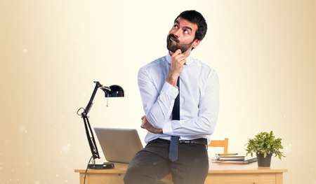 Businessman in his office thinking on ocher background